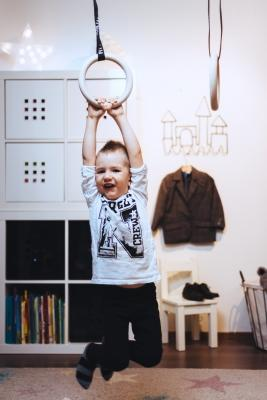 Lapsi roikkumassa FitWood GYM RINGS KIDS lasten voimistelurenkailla